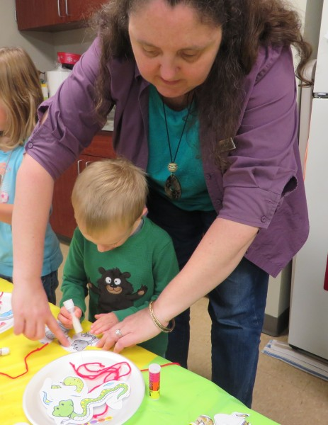Youth Librarian Mrs. Pam helps James Stull with his craft during Preschool Story Time.