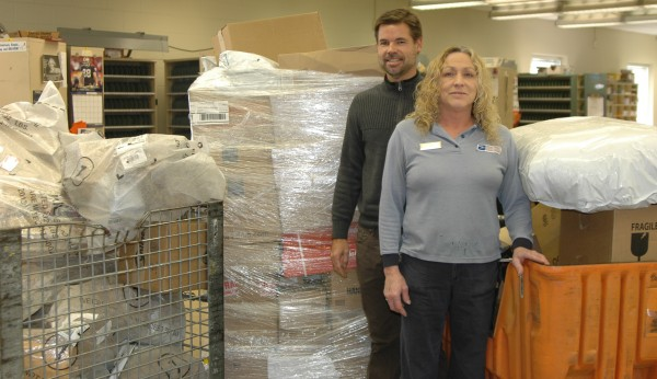 Syracuse Post Office has already seen an increase in parcels this year. Retailers have begun to push for more delivery options, according to some employees. Although most local locations will not be adding Sunday delivery, many employees will be working extra for speedy services. Pictured here are Postmaster David Bagwell (left) and USPS employee Becky Conkling.