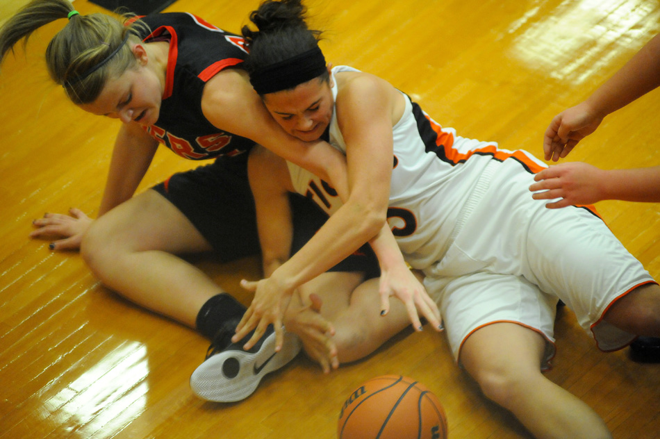 Warsaw's Page Desenberg and Fort Wayne Luers' Kathryn Knapke battle for a loose ball.