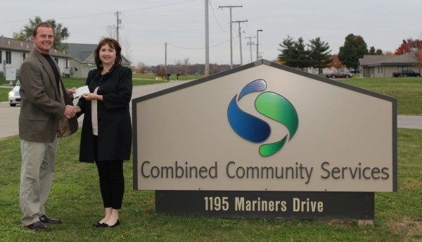 Stephen Possell, executive director of Combined Community Services, accepts a donation from Laura Campbell, with KHRA