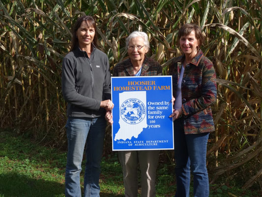 Martha Hoffman (center) with her daughters Michelle (left) and Kathy (right) in front of some of the corn grown on the farm. (Photo provided)