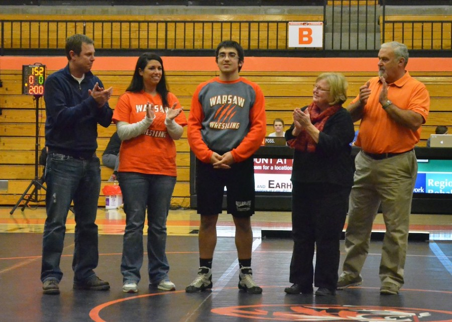 Warsaw's lone senior Rory Nolin (center), stands with his parents and grandparents prior to his match Wednesday night.