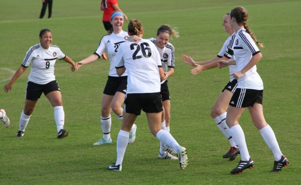 Mallory Rondeau (center) celebrates an early goal for Grace College Wednesday in the NCCAA Nationals in Florida. Rondeau, a Wawasee High School graduate, had two goals in a 3-0 victory (Photo provided by the Grace College Sports Information Department)