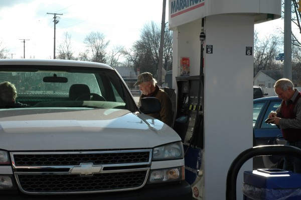 Cliff Wolf (left) tops off his tank Monday while Don Schmucker begins his transaction at the Marathon station in Milford. The station recently joined a growing list of outlets lowering their price for regular unleaded to below $2 a gallon.