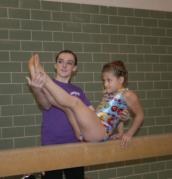 Instructor Meghan Beer helps Adelyn Holsopple on the balance beam during the annual Hot Dawg Invitational of the Wawasee Gymnastics Club, held Saturday. A second session of winter classes will be offered by the club beginning Jan. 12.