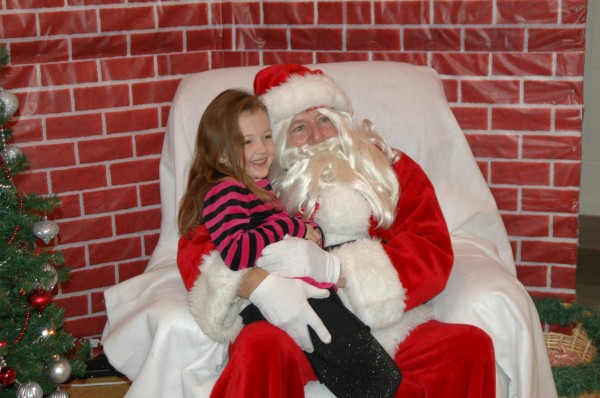 Ella Stewart, 5, sat on Santa's lap at the Syracuse Community Center's breakfast with Santa. After telling Santa what made it on her wish list this year, Stewart smiled shyly long enough for her mama to snap a cute photo, too.