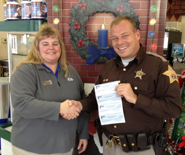 Cindy Renier presents a large donation to Chris McKeand, Kosciusko County FOP President, for the Christmas with a Cop Program. (Photo provided)