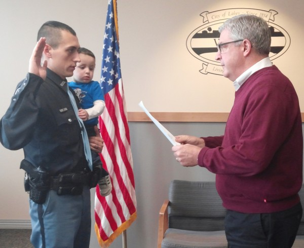 Officer Phil Hawks takes the oath of office with son Gabriel from Mayor Joe Thallemer. (Photo by Deb Patterson)