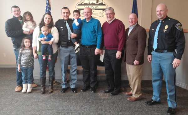 Present for the swearing in ceremony of Officer Phil Hawks were his brother, Landon Hawks; holding Officer Hawks daughter Abby; daughter Olivia, wife Becky, holding Owen; Officer Hawks holding son Gabriel, Jeff Grose, board member; Mayor Joe Thallemer; Charles Smith, board member; and Warsaw Fire Chief Scott Whitaker. (Photo by Deb Patterson)