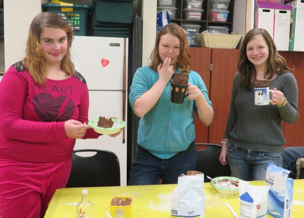 Samantha Trott, Anita Denney, and Rachel Fishburn sample their Christmas mug cakes they made during last week's Teen Time.