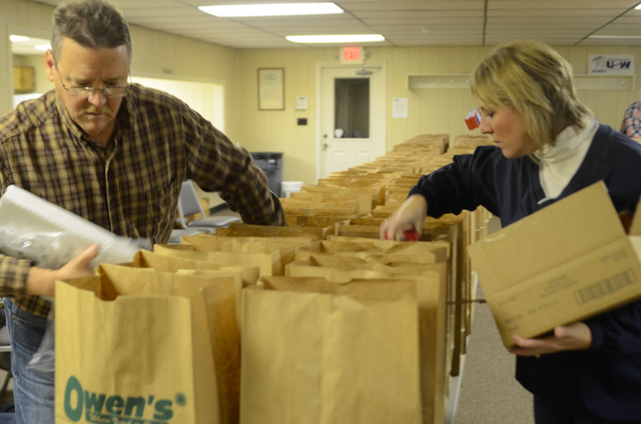Charlie Albertson and Kristy Hooker were two of about a dozen members of United Steel Workers Local 809 members bagging over 280 Christmas dinners to hand out this morning. (Photo by Deb Patterson)