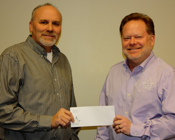 Leesburg Lions Club President Scott Kammerer accepts the donation from Maple Leaf Farms Co-President Scott Tucker.