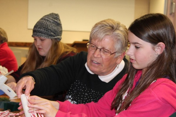 Glue guns were used to make candy cane candles at the Syracuse Library on Dec. 2. Lila Fiereck is shown making her decoration with Linda Weybright, one of the volunteers from the Homemakers Club. Emelia Layne is working on her candle behind Weybright.