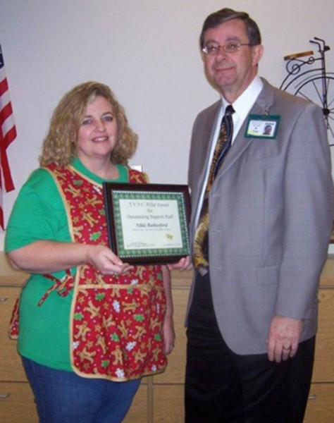 Brett Boggs presents Nikki Rutherford with a certificate of recognition.