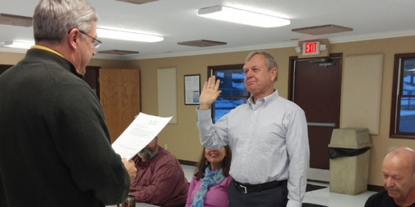 Warsaw Mayor Joe Thallemer administers the oath of office to Rick Packowski. This is Packowski's first full term as a board member. (Photo by Deb Patterson)
