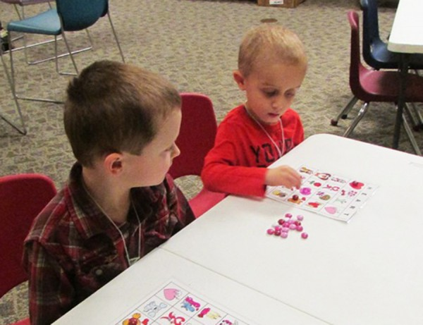 Westen Haab and Owen Morehouse focus intently as they play February Bingo for Valentines Story Time. Kids used Valentine M&M's as their bingo markers.
