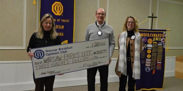 Liz McKinley of the Warsaw Parks Department receives a check from club members Rick Kerlin and Gina Voelz.
