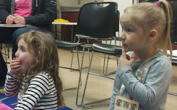 Marin Wagoner and Kaleigh Corn are captivated by the story during Preschool Story Time.