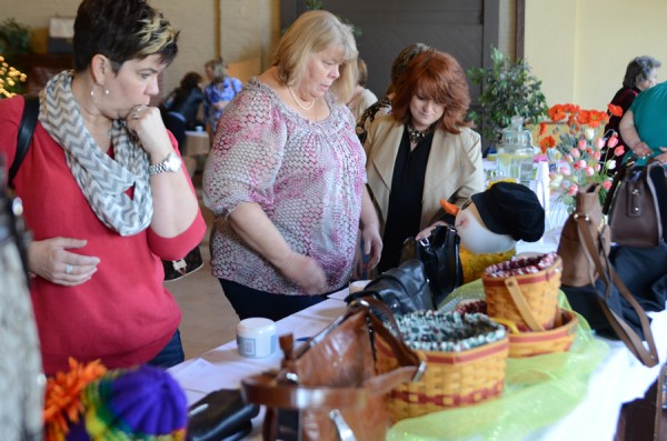 Lisa Creager, Kate Houck and Geanie Edgington view the silent auction handbags