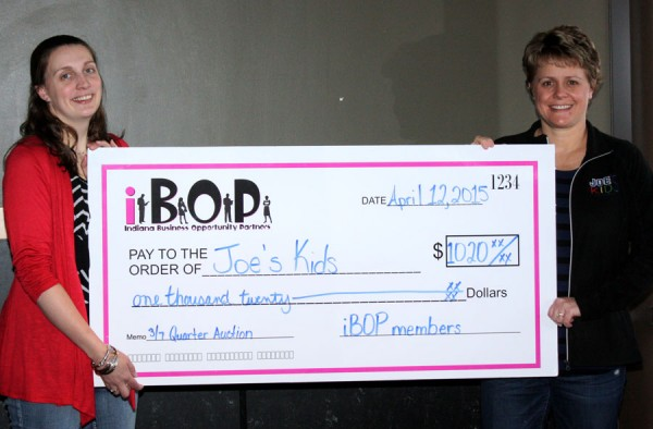 Cari Whitaker, iBOP president presents a check to Rebecca Bazzoni with Joe's Kid's, from proceeds from the March quarter auction. (Photo by Betty Swanson)