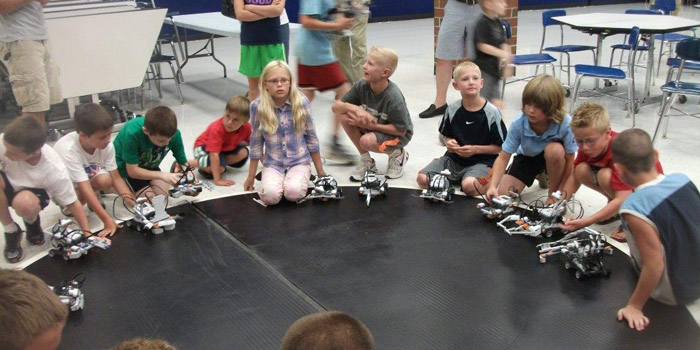 "Summer Lego Robotics Camp: Students are competing with the robots they created during summer camp in a ""robo battle""  with the winning robot pushing the other robots out of the wresting arena."
