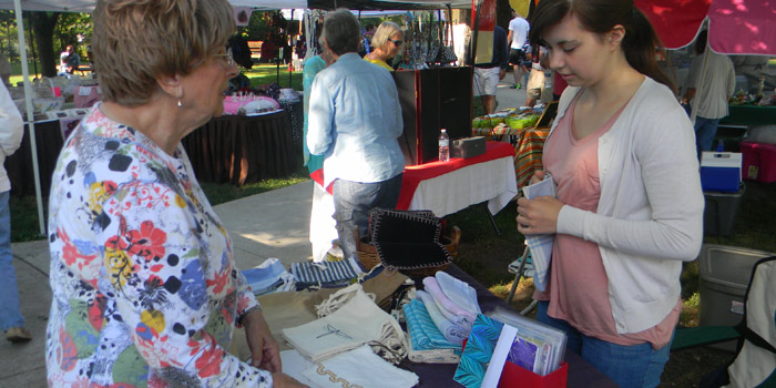 The Syracuse Artisans & Farmers Market will be one of many events occurring this Fourth of July week. Pictured, Eloise Kuhn, left, speaks with Kiara Stewart during a 2014 farmer's market.
