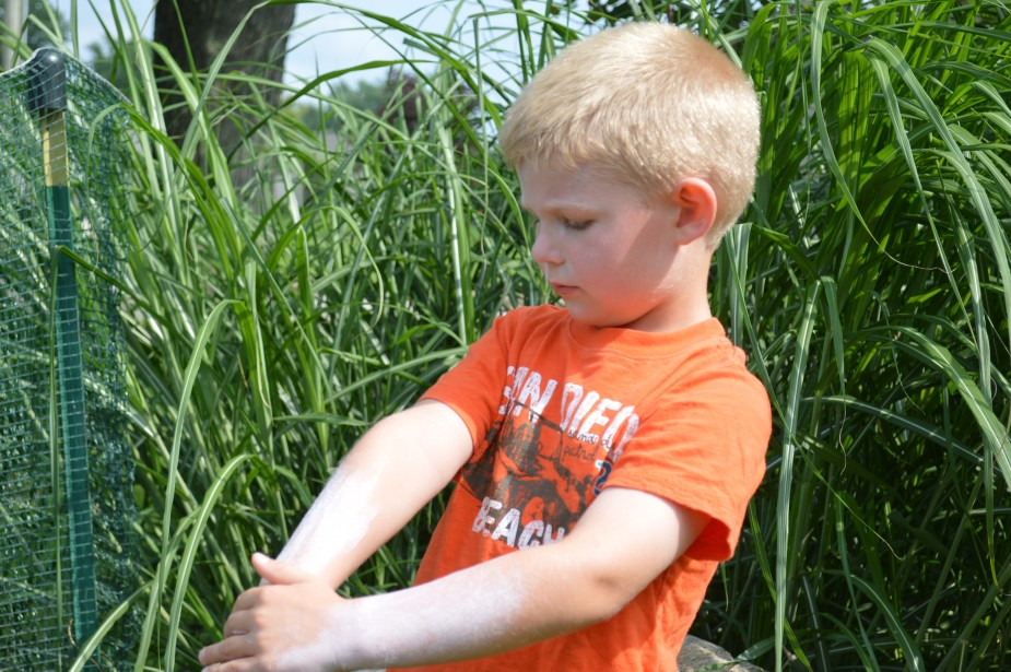 """Colten Beeler, age 4, of Warsaw slathers on the sunscreen before he goes """"froggie hunting"""" at his family's pond in Warsaw. While hunting for frogs, Colten wore a bug/sun hat to further protect his face from the sun and sunglasses to protect his eyes. Wearing adequate sun protection can reduce the risk of skin cancer."""