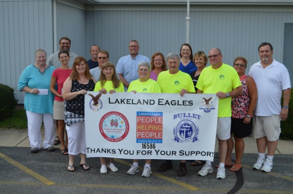 Members of the Lakeland Eagles Club pose with representatives of several local groups who received contributions from the Eagles as part of the People Helping People fundraising campaign. Pictured holding the sign (from left) are Eagles members Denise Mast, Cherri Hapner, Carol Studer, Dennis Hapner and Collin Studer. Second row: Kim Blaha, Syracuse Public Library; Ann Schlabach, Harvest With A Heart; Matt Ringler, Wawaseee Community Youth League; Traci Helton, Syracuse Food Pantry; Lori Mark, North Webster Food Pantry; LInda White, Lakeland Eagles Club; and Allen White, Lakeland Eagles Club. Third row: Mark Mast; Gavin Foster, Milford Volunteer Fire Department; Shane Bucher, Milford Fire Department and Wawasee Community Youth League; and Julie Frew, Milford Public Library. Not pictured are representatives from the North Webster Public Library, North Webster Volunteer Fire Department and Syracuse Fire Department, each of which also received donations from the Lakeland Eagles.