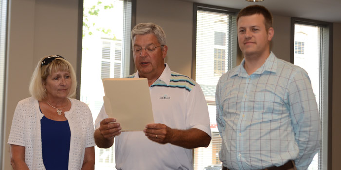 Pam Kennedy, executive director of Housing Opportunities of Warsaw, left, and Aaron Lehman, associate director of Housing Opportunities of Warsaw, listen as Mayor Joe Thallemer reads the proclamation declaring July as Fair Housing Month.