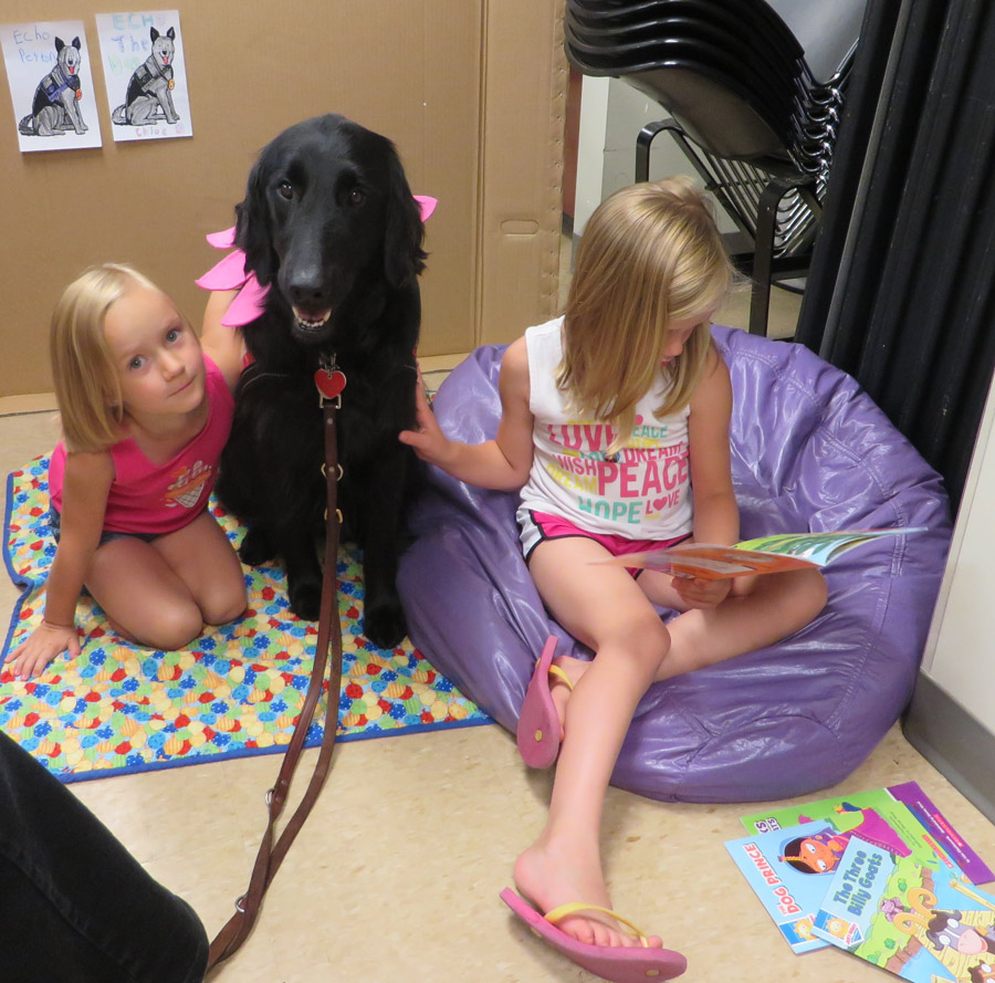 Ashlynn Corn (right) reads a story to Echo, the therapy dog, and sister Kaleigh Corn during Paws-To-Read at the North Webster Library.