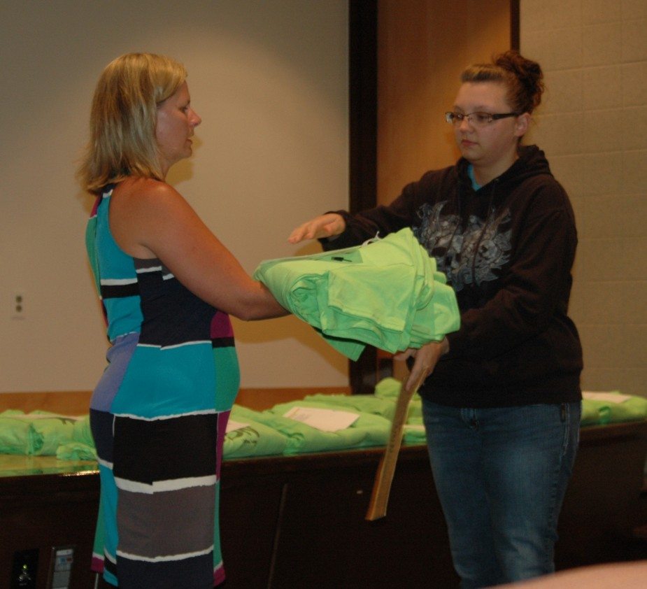 At the Day of Action kick-off meeting team leaders from the orthopedic company received their T-shirts with the new campaign logo. Five schools in Warsaw and Wawasee will be served by 250 company employees. Pictured are Tina Arlene, left, passing Christine Rogers T-shirts with the new campaign logo.