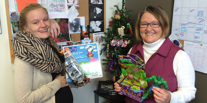 Alexis Light (left) and Peggi Lisenbee-Wright are already in the holiday spirit, preparing for Adopt-A-Family.