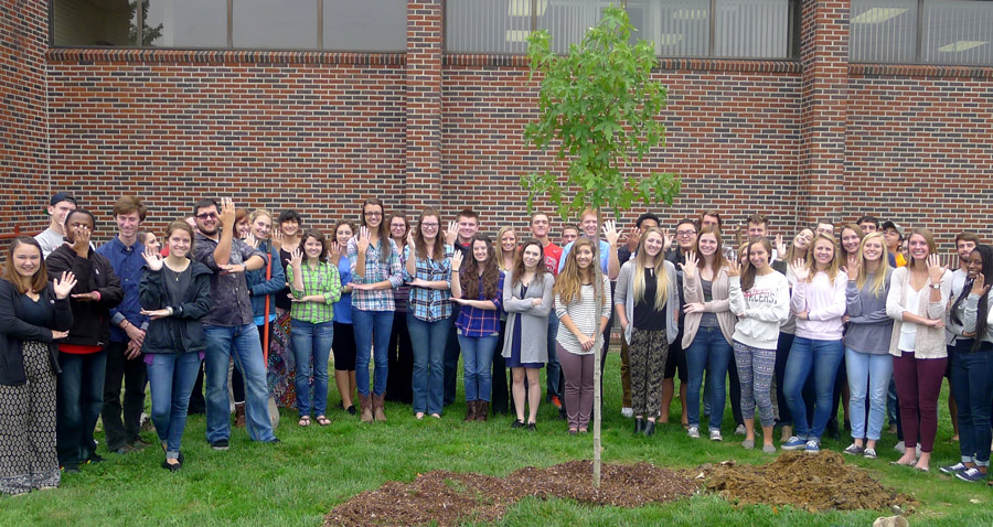 "Students from Dr. Nate Bosch's General Ecology class each make the American Sign Language sign for ""tree"" as they stand behind a sweet gum tree that was planted in front of the Cooley Science Center at Grace College."