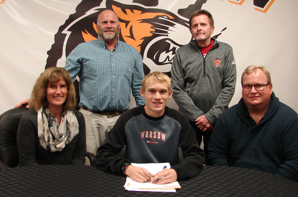 Warsaw Community High School senior Owen Glogovsky has signed a letter of intent to continue his cross country and track career at Lipscomb University. Seated with Owen are parents Jan and Terry Glogovsky. In the back row are WCHS athletic director Dave Anson and WCHS boys cross country coach Jim Mills. (Photo provided)