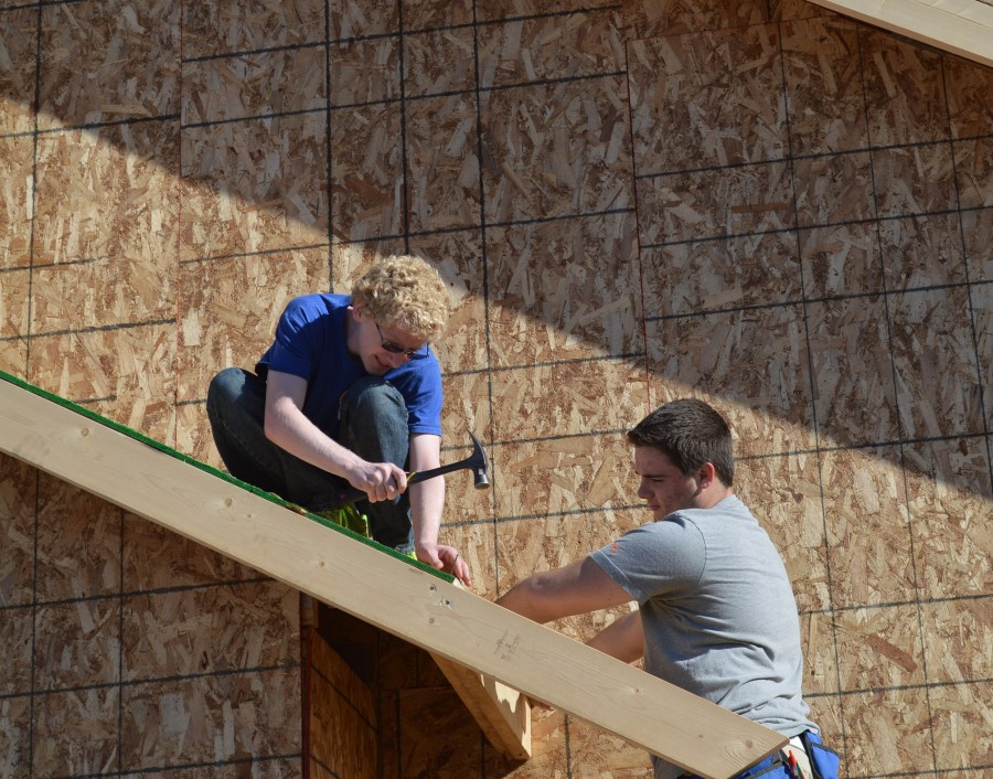 Josh Webber, left, is ready to hammer in a nail on a board being held by Brayden Spore on one of the roof lines. The two Wawasee building trades students are helping to build a home in Elkhart County.