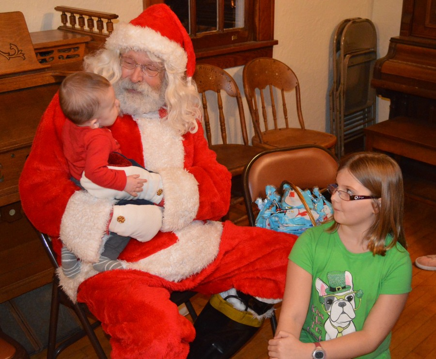 Allison Barrett watches as her brother, Toby Barrett, gave his Christmas wish list to Santa at Leesburg Town Hall. The siblings are the children of Tim and Cassandra Barrett.