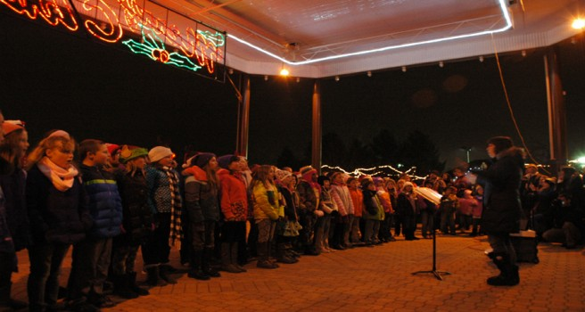 """HERALD ANGELS — Robin Merrick led a choir composed of Jefferson and Eisenhower Elementary schools at Central Park as part of the """"Light Up The Night"""" event. The choir also performed in 2013. """"It was much colder then, so I'm liking this,"""" she said. (Photo by David Hazledine)"""