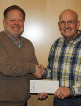 Maple Leaf Farms Co-President Scott Tucker presents a donation check to Leesburg Lions Club President Larry Kammerer. (Photo provided)