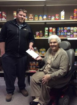 Mark Gibson, happily contributes the donation from the Woodburn Ag Center to the Woodburn Community Food Bank located in the United Methodist Church in Woodburn. Patti Shuler, director of the Woodburn Community Food Bank, is pictured accepting the donation