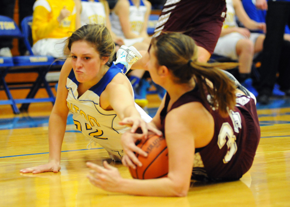 Triton's Nicole Sechrist hits the deck with Winamac's Camryn Kopa for a loose ball.