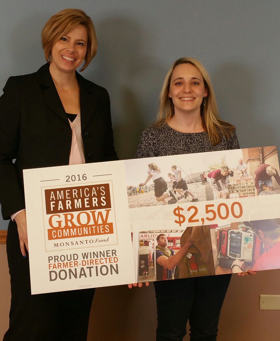 Renea Salyer, JA Area Director, left, accepts the donation from Aubrey Rife, TranzStar