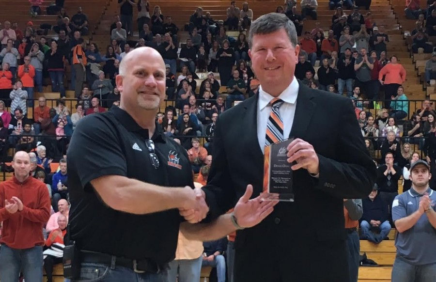 Warsaw boys basketball coach Doug Ogle (at right) was honored Saturday night for his 200th coaching win earlier this season. Ogle is congratulated by WCHS Athletic Director Dave Anson.