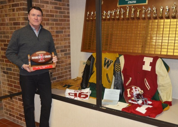 Bill Pipp poses next to the items he donated to WHS of his football playing career. Pipp is seen holding the game ball he received from IU coach John Pont after a win over Syracuse in 1972. (Photo by Nick Goralczyk)