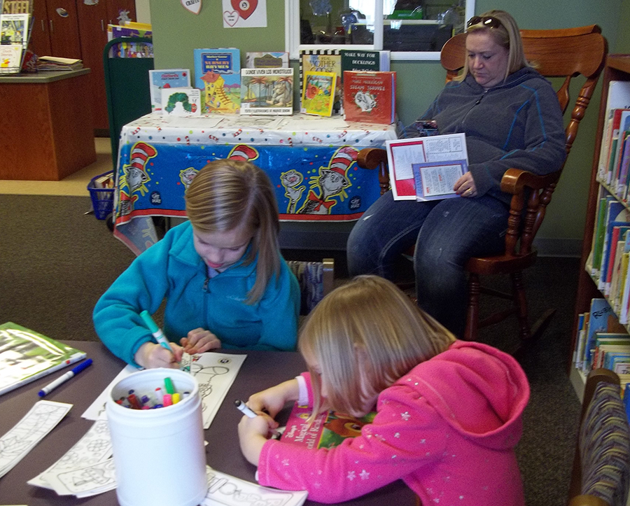 "The Corn family visited the North Webster Community Public Library during the recent ""Take Your Child to the Library Day"", an international commemoration to raise awareness of the importance of libraries in children's lives. While mom Tabatha watches, Ashlyn and Kaleigh make a craft. They also participated in a scavenger hunt to win a free book and played children's books trivia."