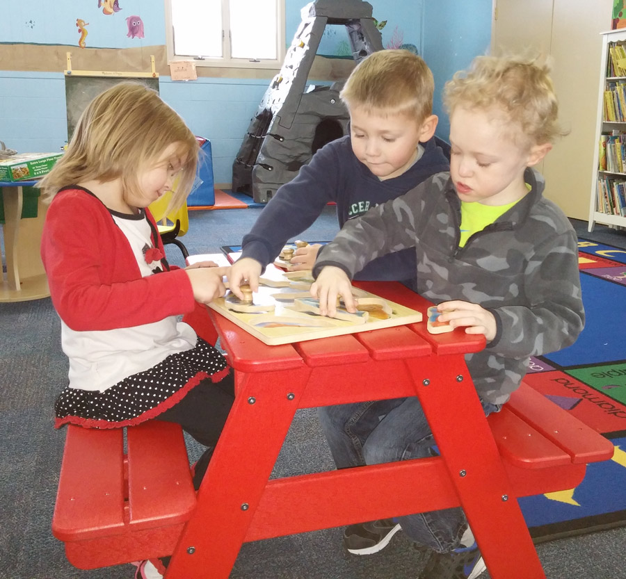 Enjoying the new picnic table to put together puzzles, from left, are Mollie Hamilton, Jaron Cantu and Oliver Compton. (Photo provided)