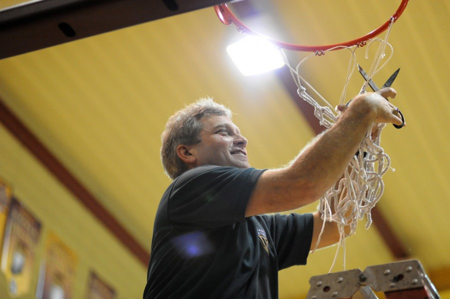 Wawasee girls basketball coach Kem Zolman cuts down the net in 2011 after his team won a sectional title at Columbia City. Zolman retired on Wednesday after 18 years as the Warriors' coach (File photos by Mike Deak)
