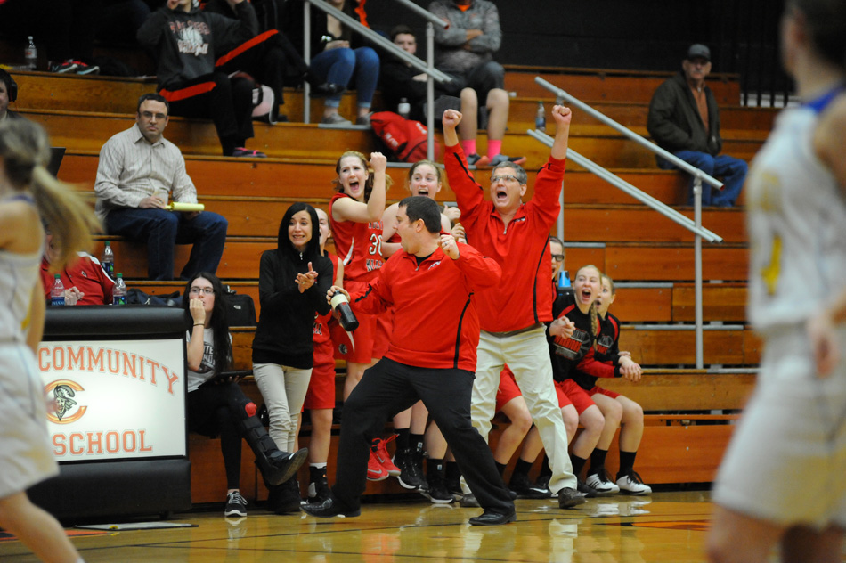 North Miami head coach Ryan DeMien, center, celebrates with several excited Warriors after Triton turned the ball over in the final seconds of North Miami's 31-29 come-from-behind win Tuesday night at the Culver Girls Basketball Sectional. (Photos by Mike Deak)