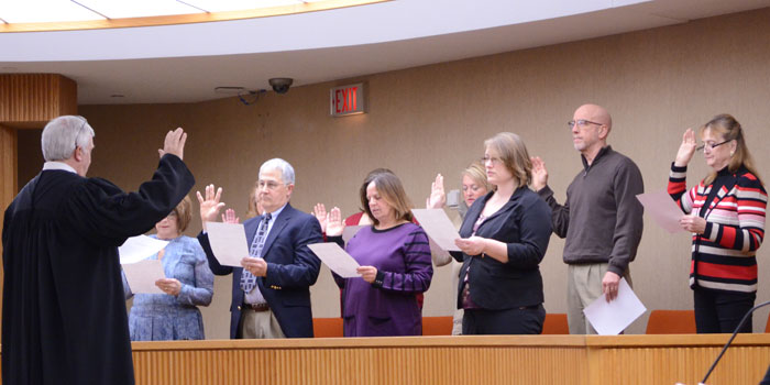 Judge David Cates swears in nine new CASA volunteers.