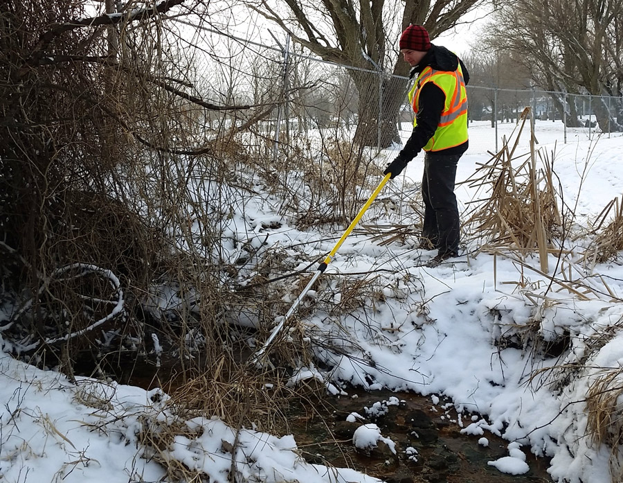 Research assistant Seth Bingham samples stormwater outfall flowing to Pike Lake. This sampling effort is important in light of recent rain and storm events in Kosciusko County.
