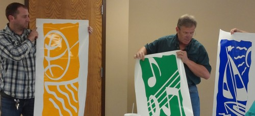 Shawn Gardner, maintenance diretor; Larry Plummer, park superintendent; and Sheila Wieringa, recreation director, hold up three banners which have the three elements of the department's logo: sports, music and recreation.